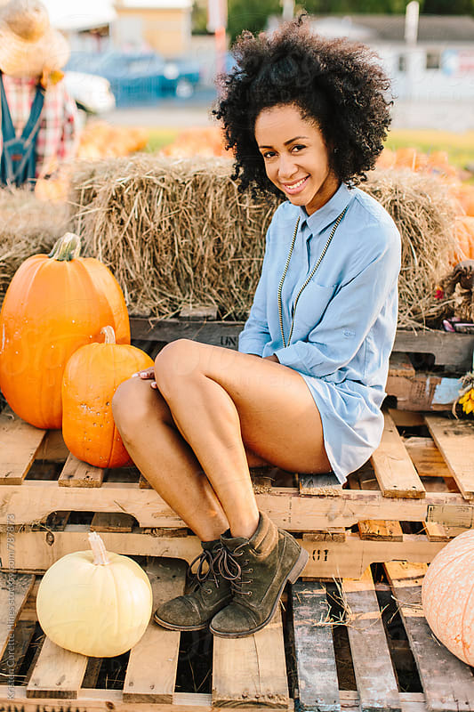 A beautiful woman posing infront of a pumpkin patch setup by Kristen Curette Hines for Stocksy United
