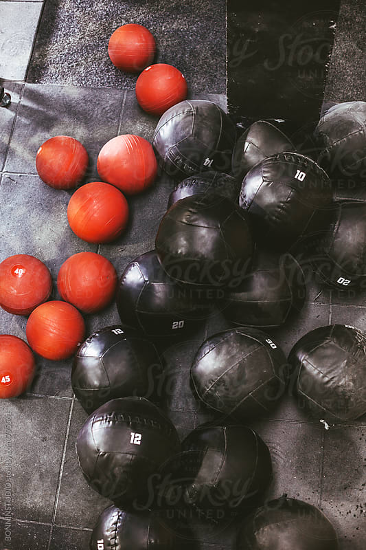 Red and black weighted balls in a gym. by BONNINSTUDIO for Stocksy United