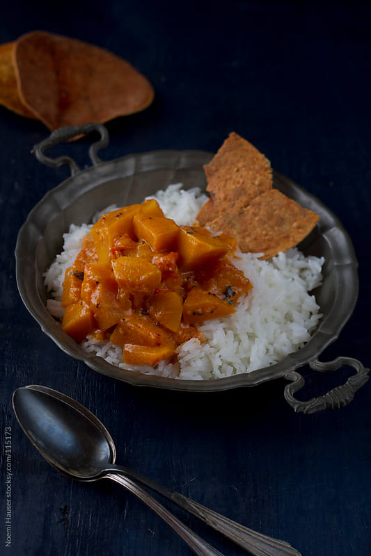 Pumpkin curry with rice and papadums by Noemi Hauser for Stocksy United