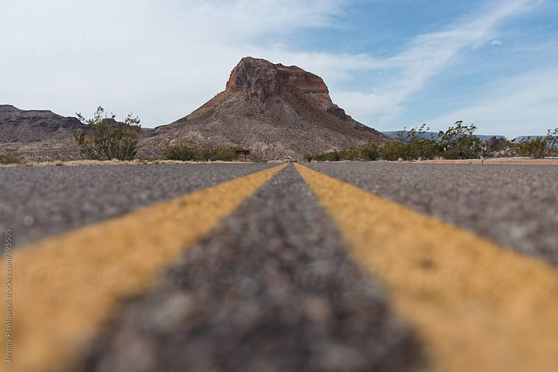 Low shot of road leading to mountain in the desert by Jeremy Pawlowski for Stocksy United