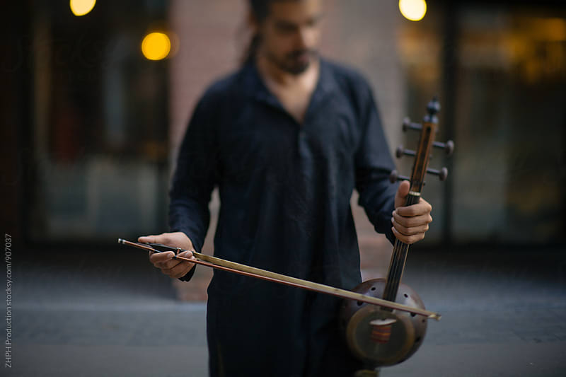 Musician holding kamancha by Artem Zhushman for Stocksy United