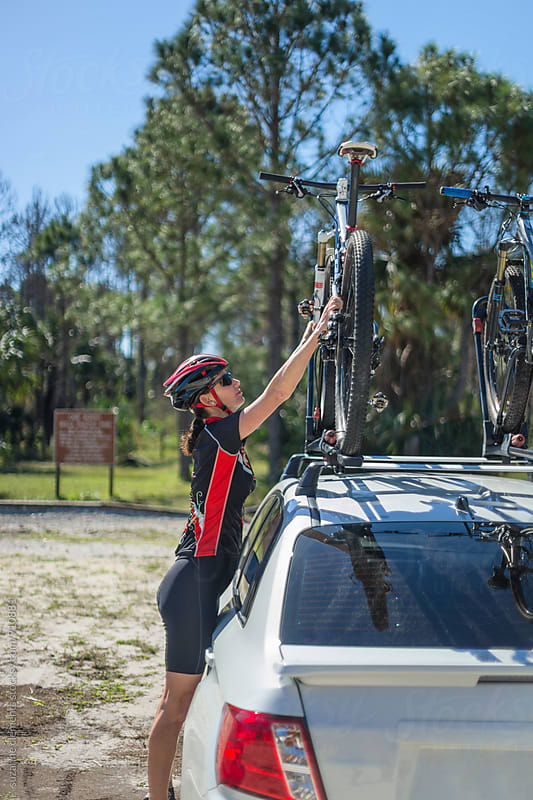 Woman Mountain Biker Gets Bike off Bike Rack by suzanne clements for Stocksy United