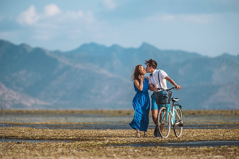 Young Couple Riding Bike by Alexander Grabchilev for Stocksy United