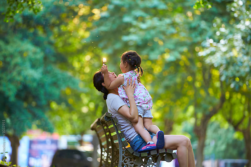 happy little asian girl playing with her mother in the park by Bo Bo for Stocksy United