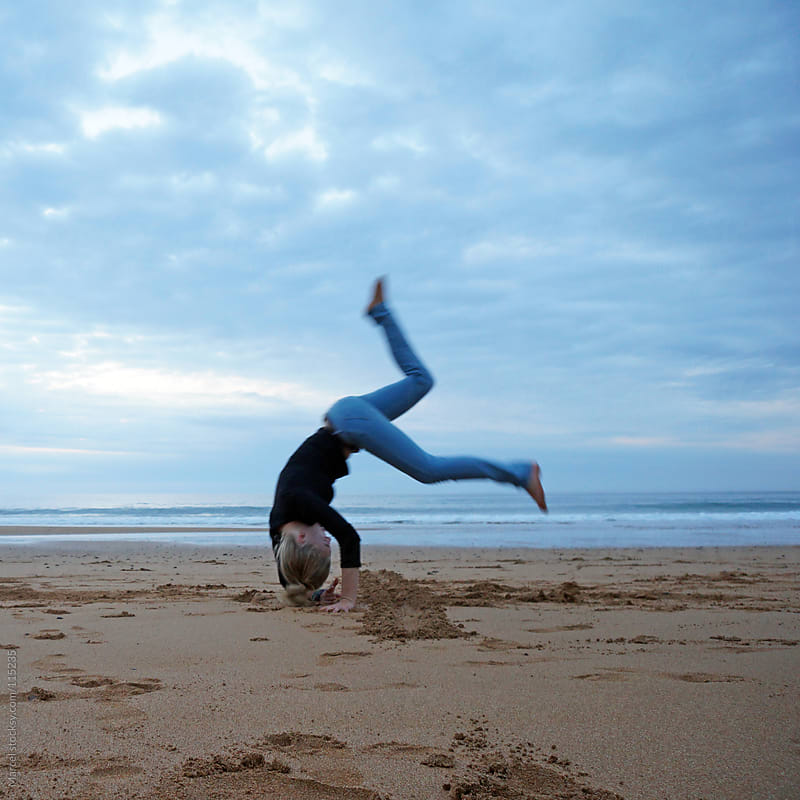 Girl making somersault jump on the beach in Spain by Marcel for Stocksy United