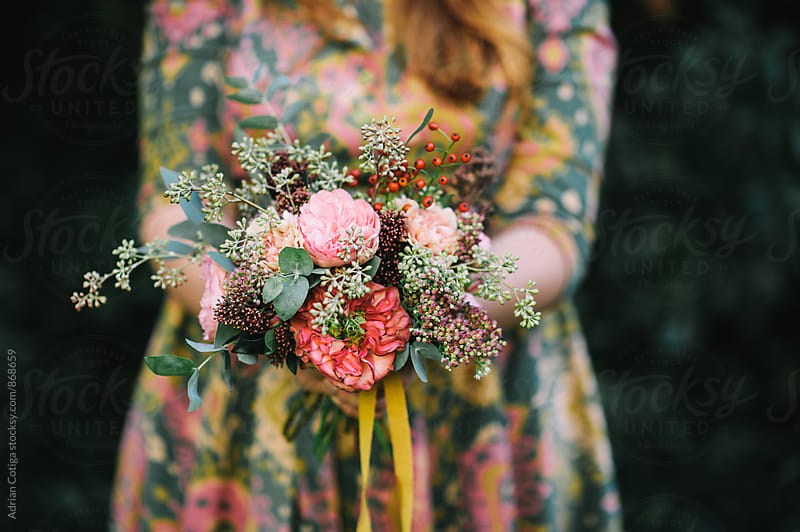 Woman holding a lovely bouquet of pink peonies and eucalyptus by Adrian Cotiga for Stocksy United