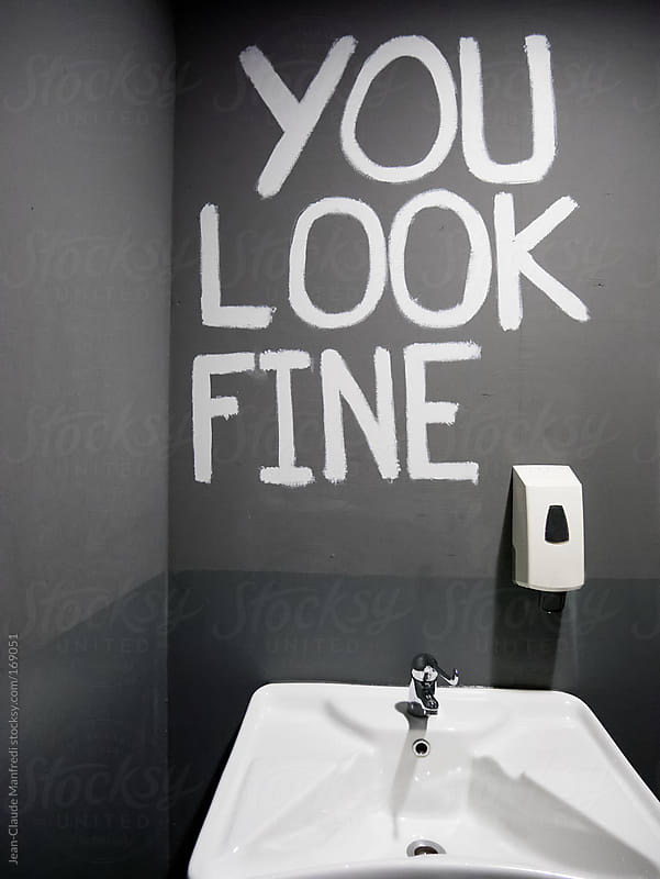 Sign on a wall saying: you look fine. Toilet where you do not need the mirror by Jean-Claude Manfredi for Stocksy United