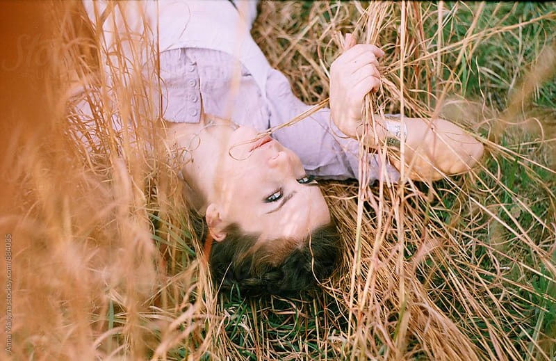 A film portrait of young beautiful woman lying at the grass by Anna Malgina for Stocksy United