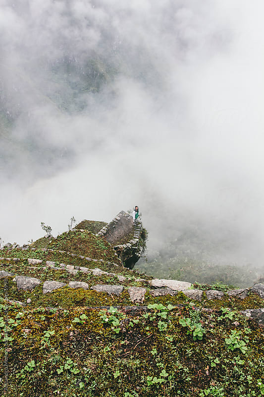 Young man on ancient ruins terrace over clouds - Machu Picchu, Peru by Alejandro Moreno de Carlos for Stocksy United
