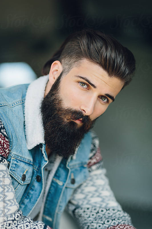 Handsome bearded man looking at the camera by Amir Kaljikovic for Stocksy United