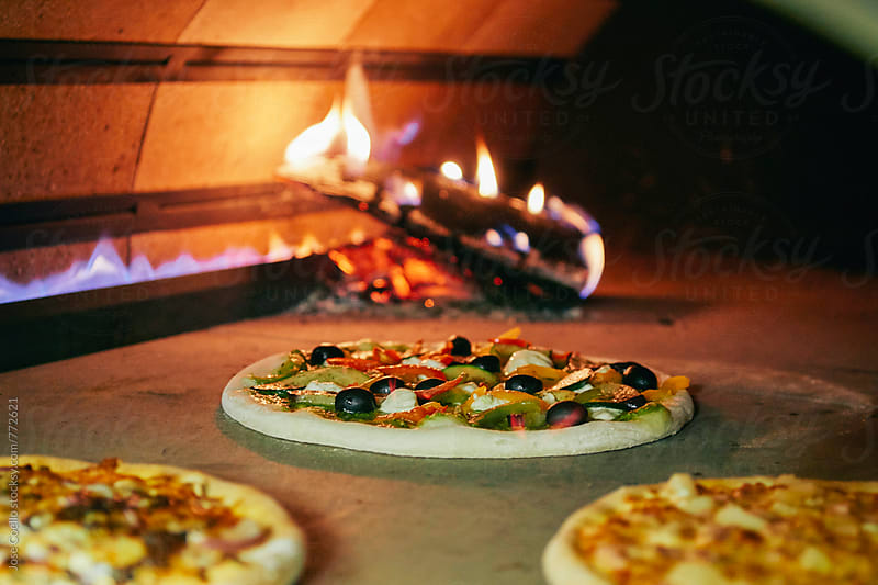 Pizza into the wood oven by Jose Coello for Stocksy United