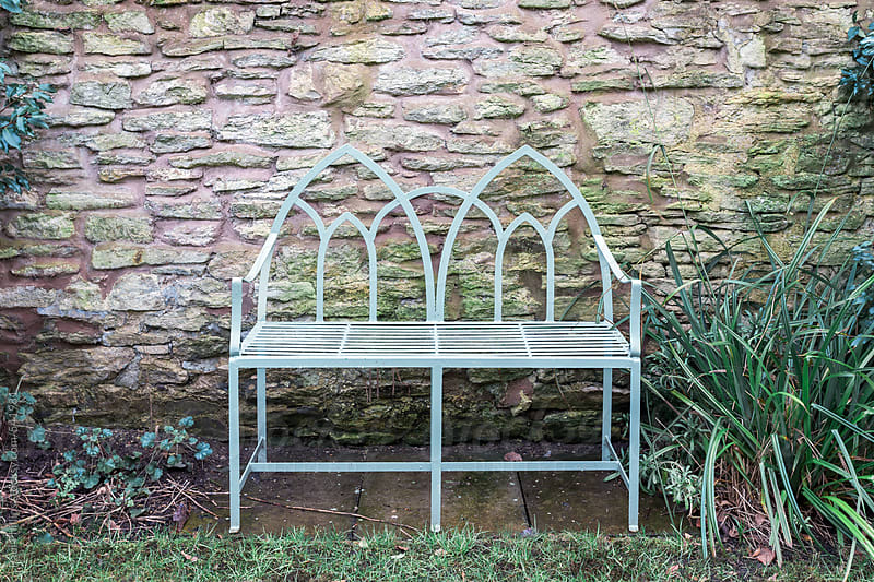 Two person metal garden bench beside a stone wall by Paul Phillips for Stocksy United