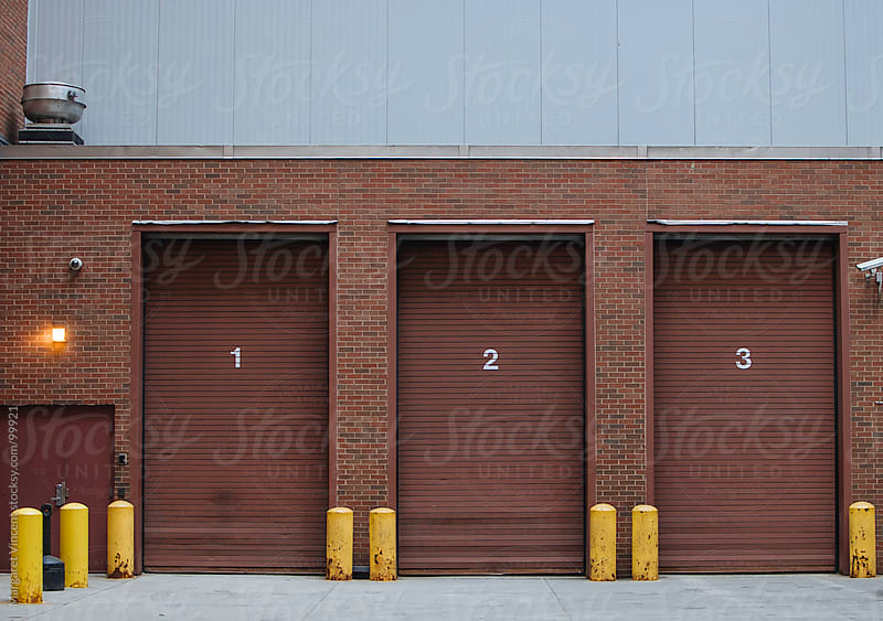 three numbered garage doors by Margaret Vincent for Stocksy United