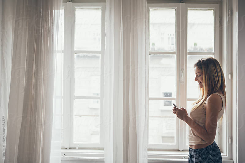 Woman Texting by the Window by Lumina for Stocksy United