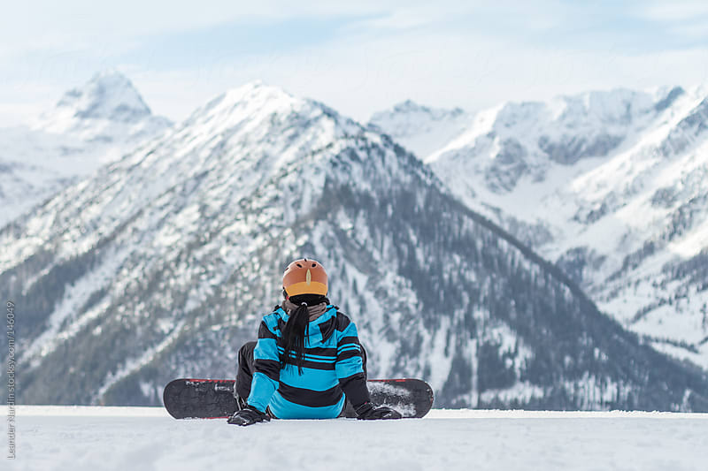 female snowboarder sitting in the snow by Leander Nardin for Stocksy United