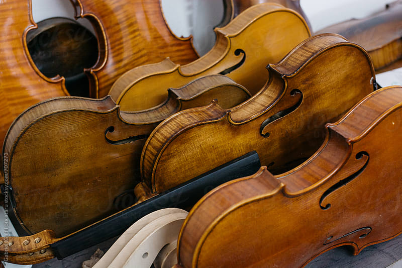 Various violin bodies to be repaired in a shop by Gabriel (Gabi) Bucataru for Stocksy United