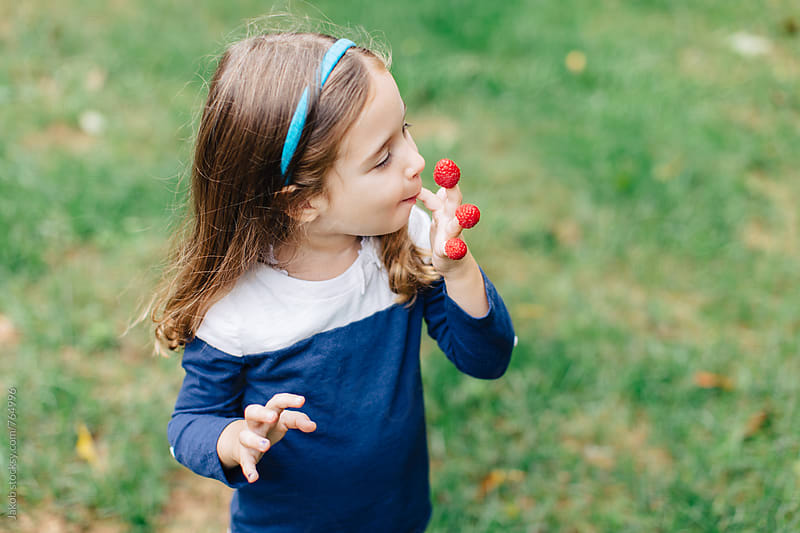 Cute young girl eating raspberries of her fingers  by Jakob for Stocksy United