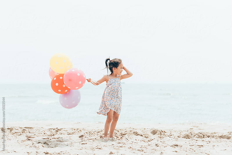 Cute toddler girl holding balloons on the seaside by Maa Hoo for Stocksy United
