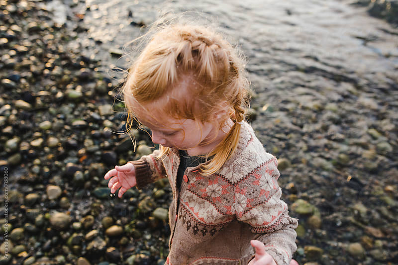 A Little girl dripping with water stands on the rocky shore by Amanda Voelker for Stocksy United