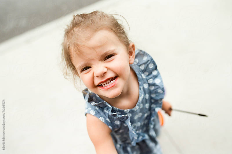 little girl smiling at the camera by Maria Manco for Stocksy United