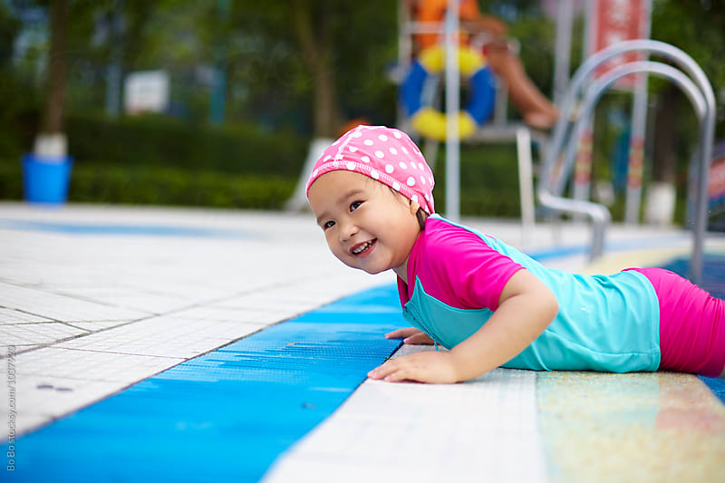 lovely little asian girl having fun in the swimming pool by Bo Bo for Stocksy United