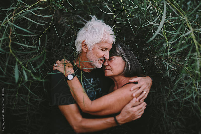 Old couple embracing in the branches by Evgenij Yulkin for Stocksy United
