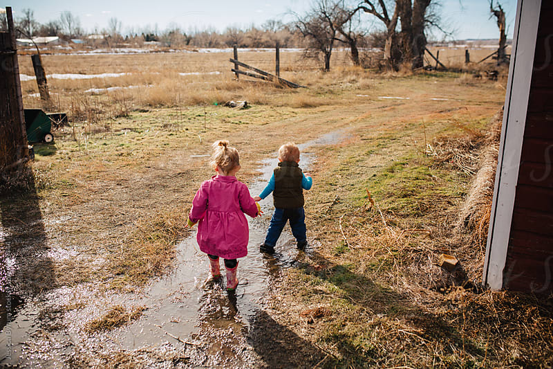 Toddler siblings walking through mud puddle on farm by Jessica Byrum for Stocksy United