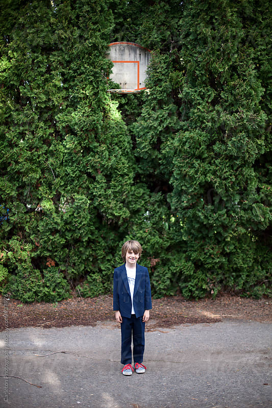 Boy in suit stands beneath basketball hoop in alley by Carleton Photography for Stocksy United