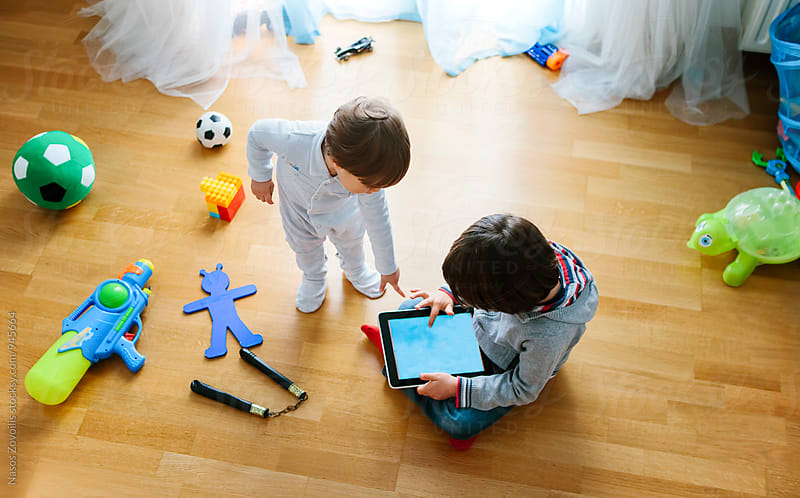 1 year old boy and his 5 years old brother looking a digital tablet by Nasos Zovoilis for Stocksy United