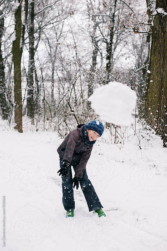 Boy throwing a huge snowball toward the camera. by Lea Csontos for Stocksy United