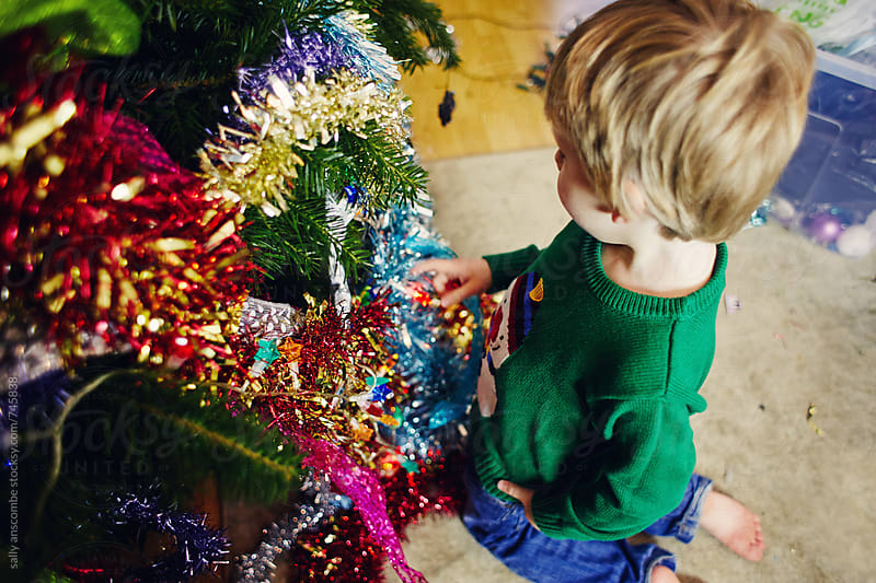Child decorating a Christmas tree by sally anscombe for Stocksy United