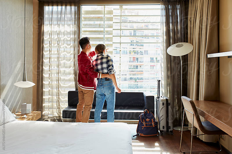 Loving Couple Looking Through Window Of Hotel Room by ALTO IMAGES for Stocksy United