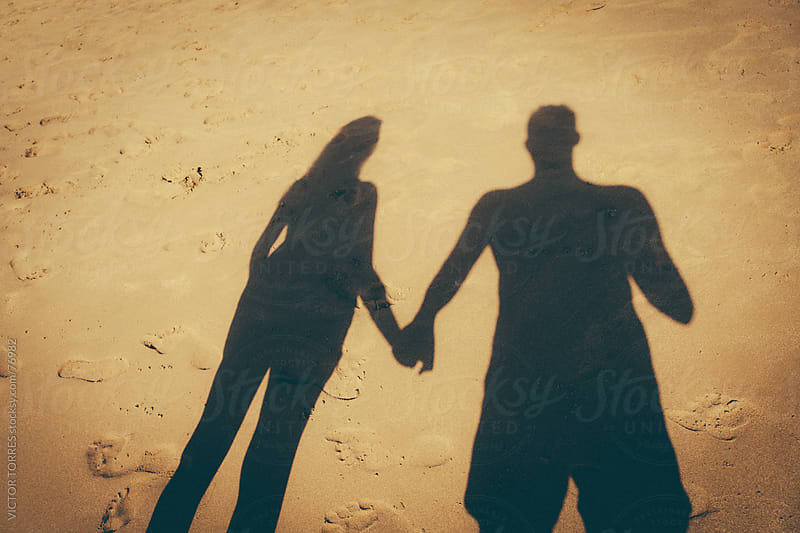 Couple Shadow Join Hands on the Beach Sand by VICTOR TORRES for Stocksy United