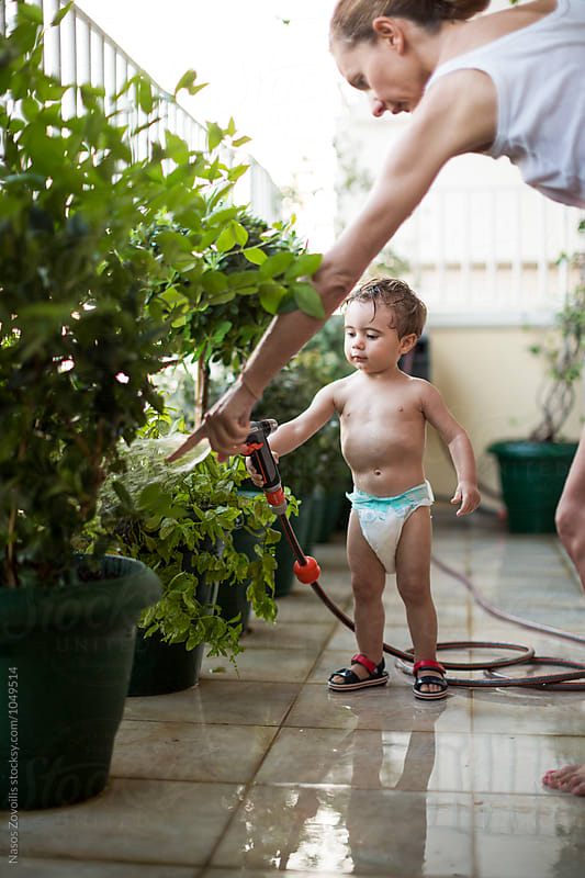 Mother and her 1 year old son playing with water by Nasos Zovoilis for Stocksy United