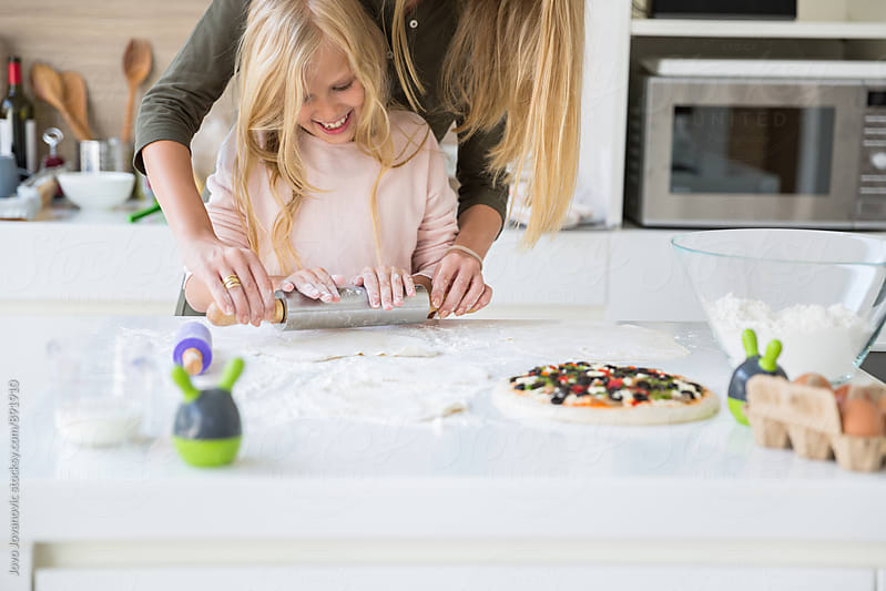 Mother and daughter using a rolling pin together in the kitchen by Jovo Jovanovic for Stocksy United