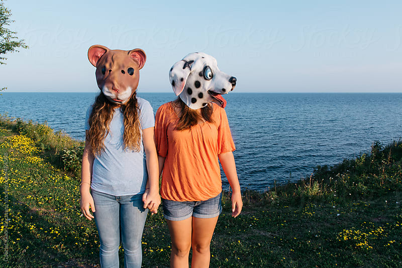 Two young girls with dog and squirrel masks by Gabriel (Gabi) Bucataru for Stocksy United