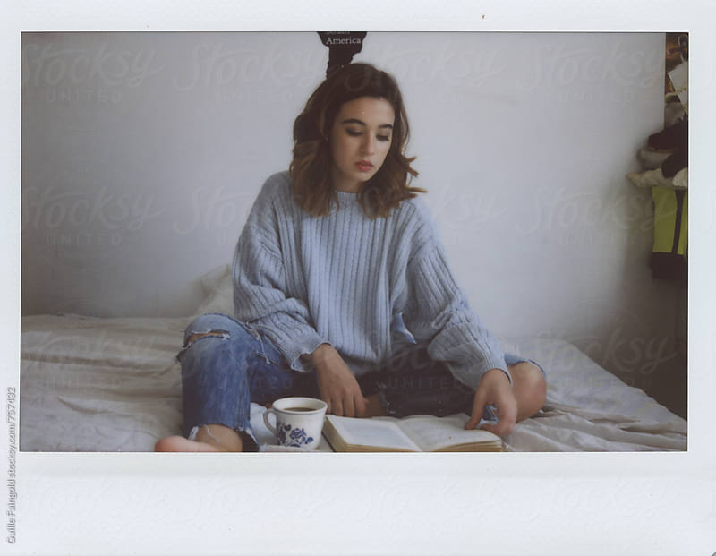 young woman reading a book on her bedroom by Guille Faingold for Stocksy United