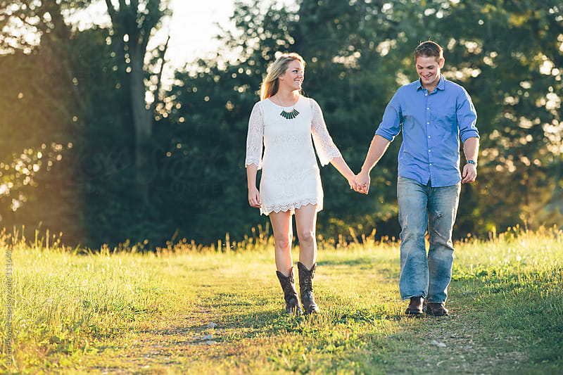 young couple walking in the country  by Brian Powell for Stocksy United