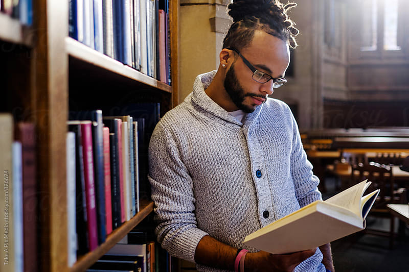 Male African American college student reading and studying in the library by Suprijono Suharjoto for Stocksy United
