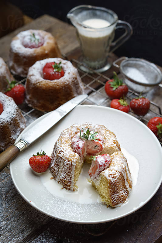 Serving of strawberry bundt cake with cream on a plate. by Darren Muir for Stocksy United