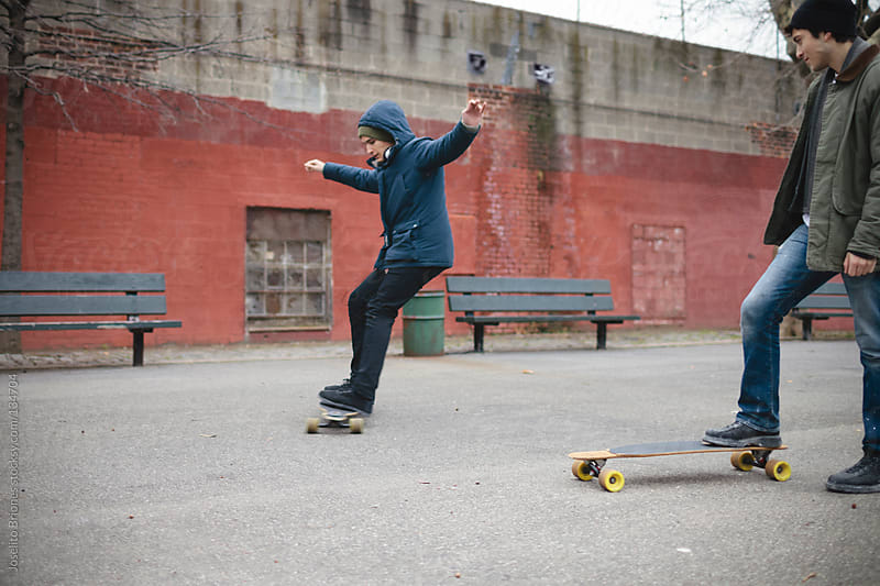 Mexican-American Young Men Friends in Brooklyn Playground with Skateboard by Joselito Briones for Stocksy United