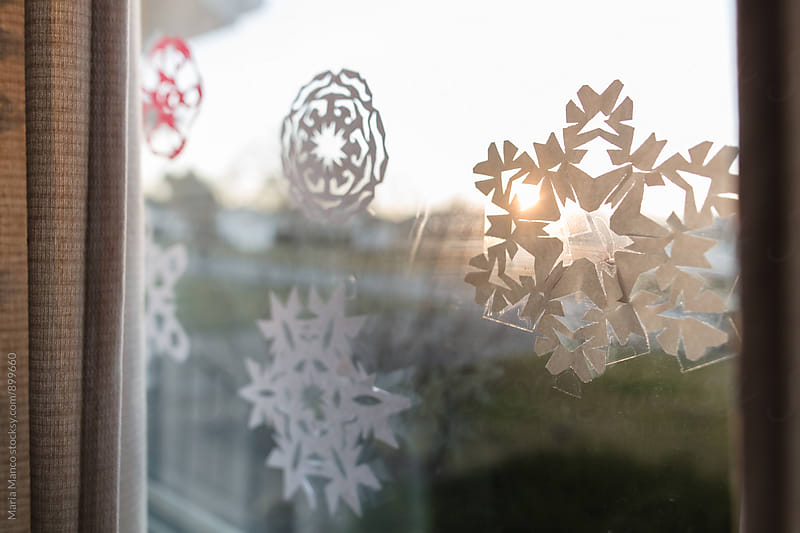 Paper Snowflake cutouts on a window by Maria Manco for Stocksy United