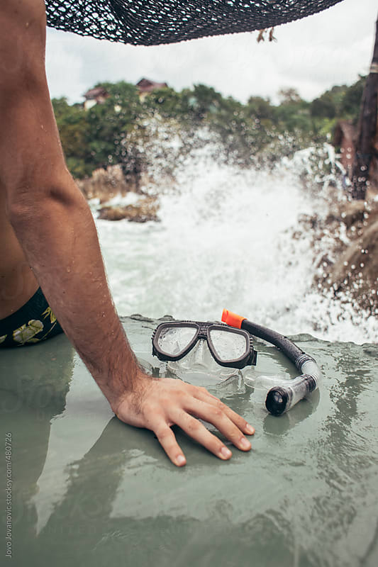 Man and his snorkelling mask on a cliff looking out at splashing waves and nature by Jovo Jovanovic for Stocksy United