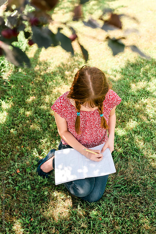 teen girl doing homework under a tree by Deirdre Malfatto for Stocksy United
