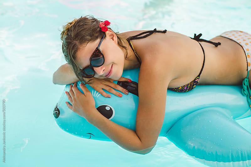 Beautiful young woman in bikini relaxing in the pool by Aleksandra Jankovic for Stocksy United