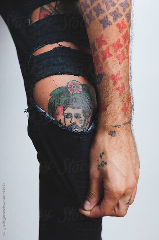 Male Gypsy Tattoo on the Knee, Seen Through Ripped Pants by Giorgio Magini for Stocksy United