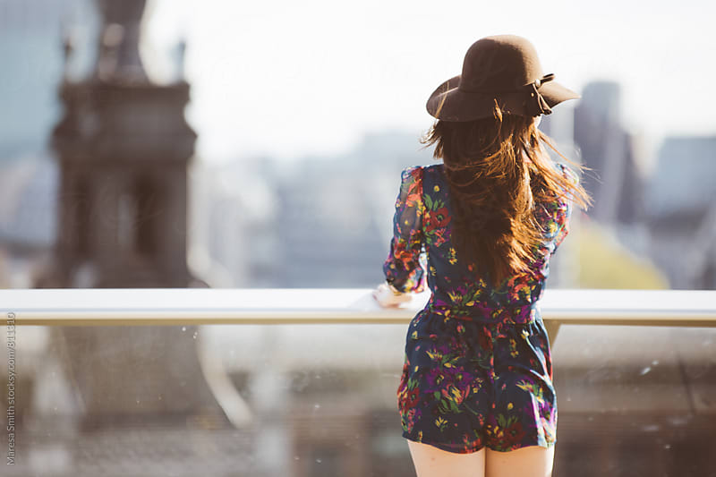 A brunette girl wearing a hat looks out over the city in the afternoon light by Maresa Smith for Stocksy United
