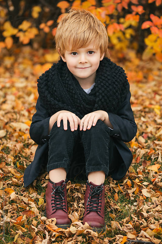 A young boy sitting on a ground covered with fall leaves smiling at camera by Ania Boniecka for Stocksy United