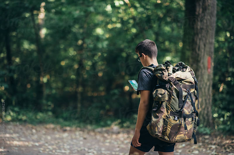 Young teen boy with a backpack exploring the forest, and using smartphone by Adrian Cotiga for Stocksy United