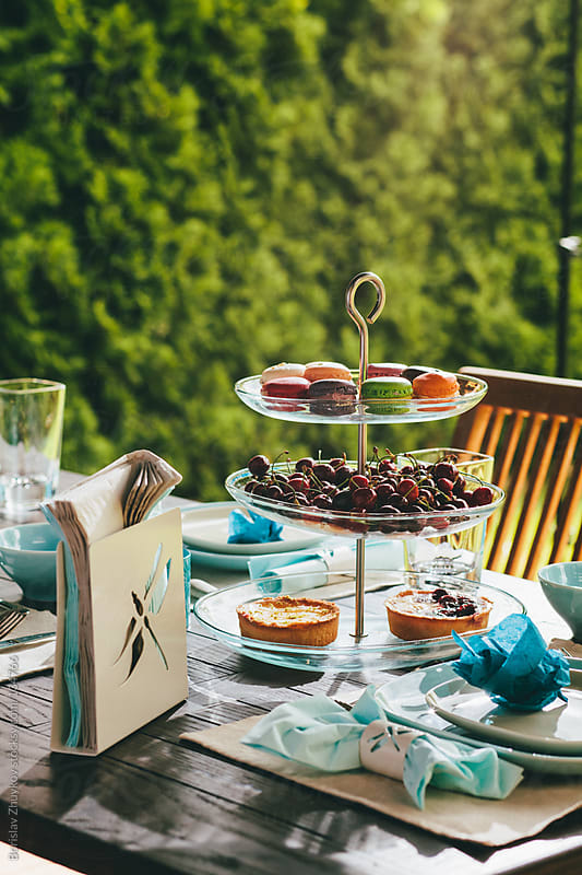 Beautifully decorated wooden table with food and desserts by Borislav Zhuykov for Stocksy United